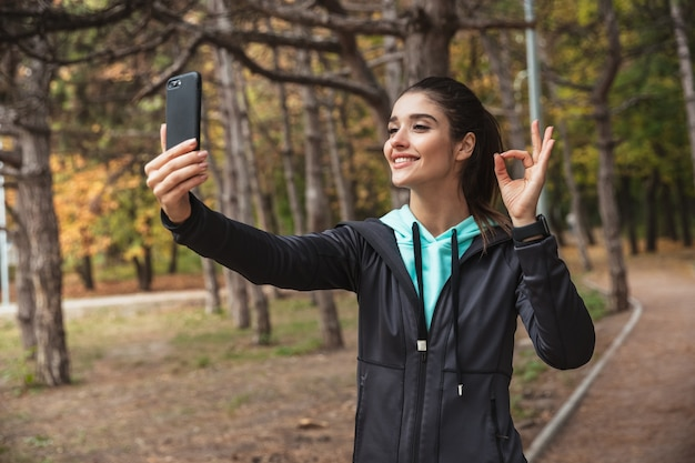 Photo of amazing young pretty fitness woman outdoors in the park using mobile phone take a selfie with okay gesture.