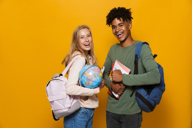 Photo of american and caucasian students man and woman 16-18 wearing backpacks holding earth globe, isolated over yellow background