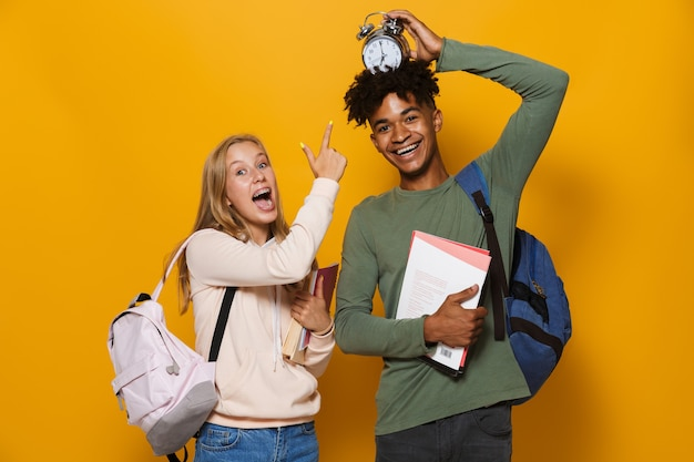 Photo of amusing students man and woman 16-18 wearing backpacks holding exercise books and alarm clock, isolated over yellow background