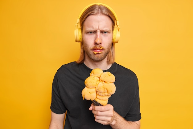 Photo of angry bearded man has sulking displeased expression smeared face with ice cream hears bad news listens music wears stereo headphones on ears holds appetizing gelato poses indoor alone