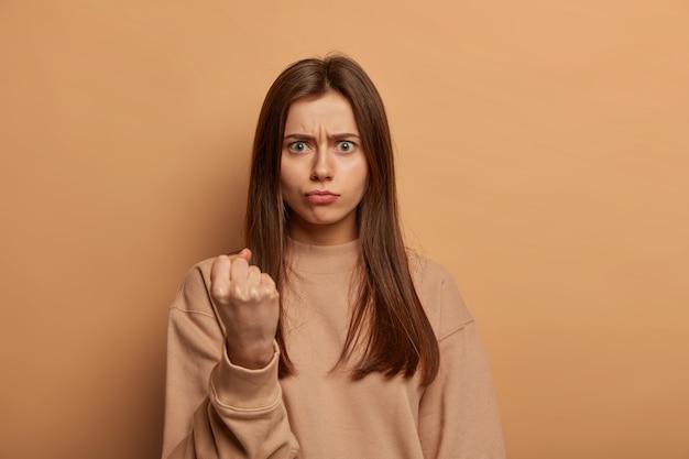 La foto della donna caucasica arrabbiata stringe il pugno, viene a discutere, si lamenta del rumore, guarda arrabbiata la telecamera