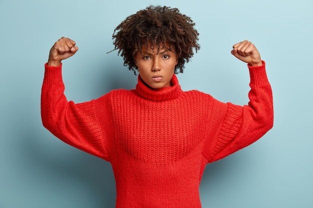 Photo of angry furious afro american woman keeps arms raised, clenches fists, shows muscles