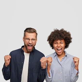 Photo of angry mixed race young students clench fists with annoyance, shout desperately