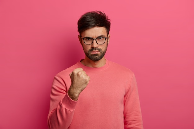 Photo of angry unshaven man clenches fist, looks with irritation , promises to punish colleague for being late, wears casual clothes, poses in  against bright pink wall.