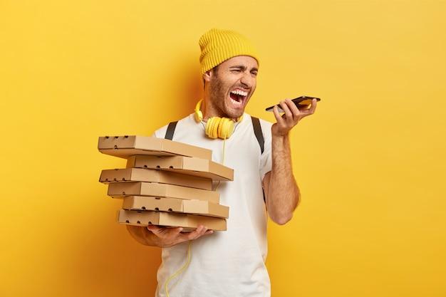 La foto del corriere infastidito dell'uomo della pizza urla con rabbia allo smartphone, ha una conversazione fastidiosa con il cliente, tiene una pila di scatole di cartone, indossa un cappello e una maglietta bianca, isolato sul muro giallo