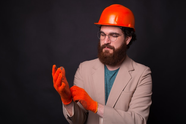 Photo of architector wear gloves and preparing for inspection stading over dark background