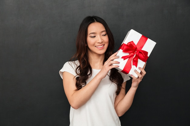 Photo of asian curious woman in casual t-shirt rejoicing her birthday box, isolated over dark gray wall