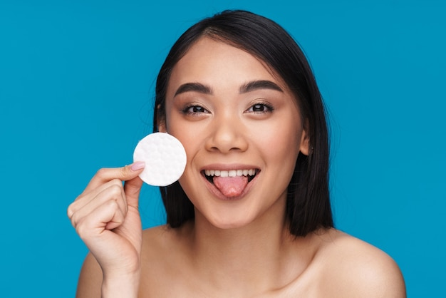 Photo of asian happy positive pretty young woman posing isolated on blue wall with skin cleansing cotton pad showing tongue.