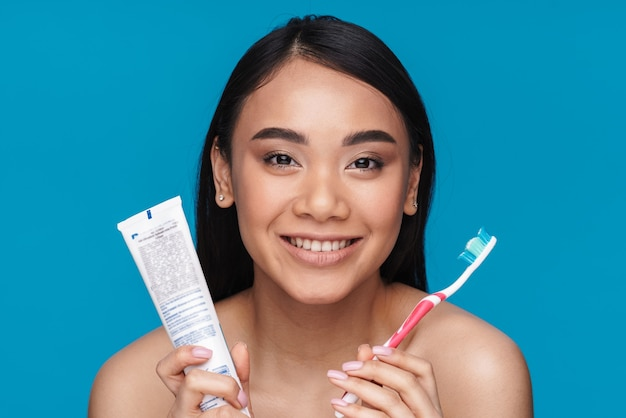 Photo of asian happy smiling young woman posing isolated on blue wall holding toothbrush and paste.
