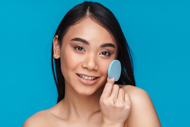 Photo of asian pleased optimistic pretty young woman posing isolated on blue wall with skin cleansing sponge.