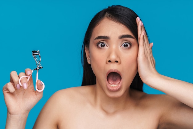 Photo of asian shocked surprised young woman posing isolated on blue wall holding eyelash curler.