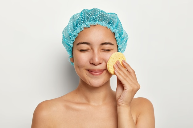 Photo of asian woman cleans face with cellulose sponge, cares about skin, has cosmetology treatments, eyes closed, stands with bare body, stands against white wall. spa procedures, makeup removal