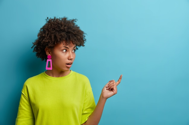 Photo of astonished curly haired woman points to side copy space with shocked expression, shows blank wall for idea presentation, dressed casually demonstrates crazy