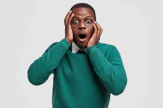 La foto di un ragazzo dalla pelle scura attonito apre ampiamente la bocca, esclama con espressione inorridita, vestito con un maglione verde, reagisce a una notizia improvvisa