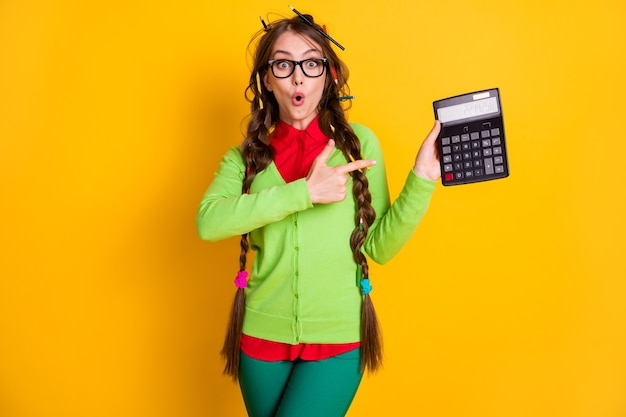 Photo of astonished girl with messy hairstyle point finger calculator isolated on bright color background