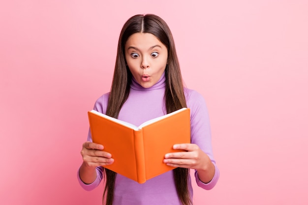 Photo of astonished latin kid girl read  textbook wear purple jumper isolated over pastel color background