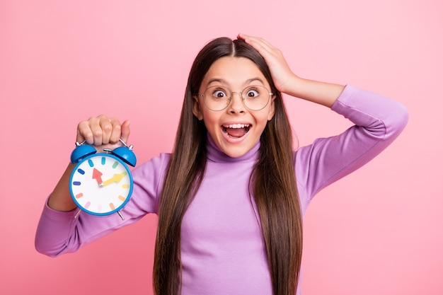 Photo of astonished little kid hold clock touch hand head isolated over pastel color background
