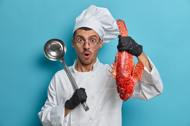Photo of astonished male chef tries best fish recipes, holds red sea bass, ladle, wears cook hat and white uniform