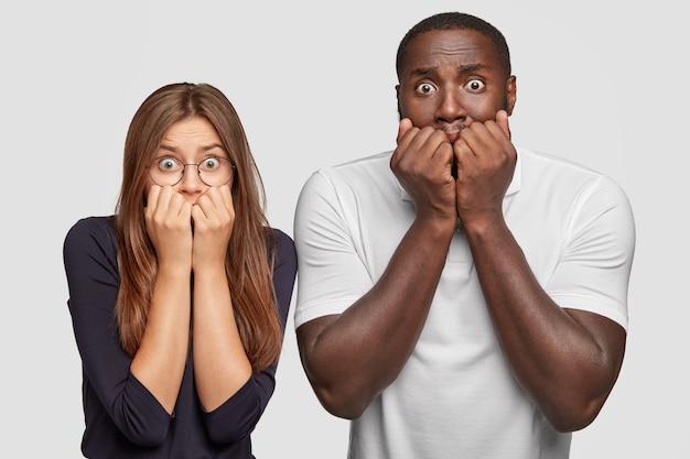 Foto di due uomini e una donna interrazziali stupiti perplessi tremano di grande paura