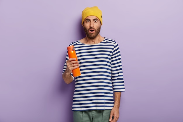 La foto del giovane con la barba lunga stupito indossa un cappello giallo alla moda, un maglione a strisce