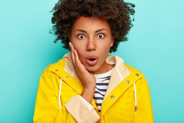 La foto di una donna sbalordita ha il fiato sospeso, fissa con occhi spalancati, reagisce in modo scioccante, ha un'acconciatura afro, indossa un impermeabile giallo, isolato su sfondo blu, rimane senza parole