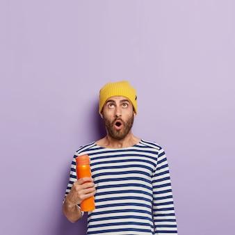 La foto del giovane modello maschio stupito si è concentrata verso l'alto, tiene un thermos arancione, indossa un maglione a righe e un cappello giallo, ha un'espressione sorpresa