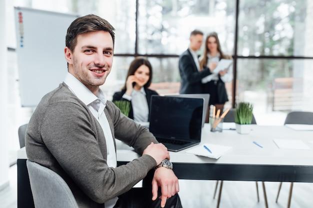彼のチームがオフィスで働いている成功したハンサムなビジネスマンの写真。