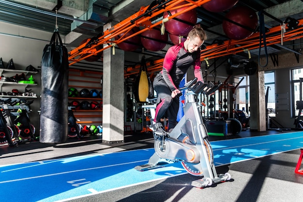Photo of the athlete is engaged on a cardiovascular equipment in a fitness center in sunny weather.