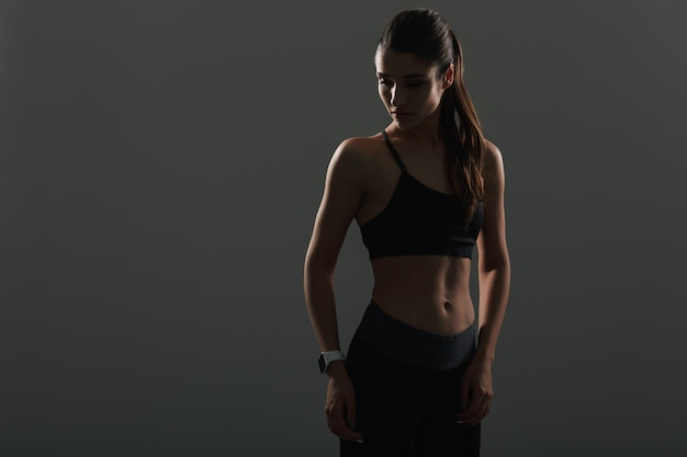 Photo of athletic pretty woman looking aside while posing  with wristwatch, isolated over dark wall