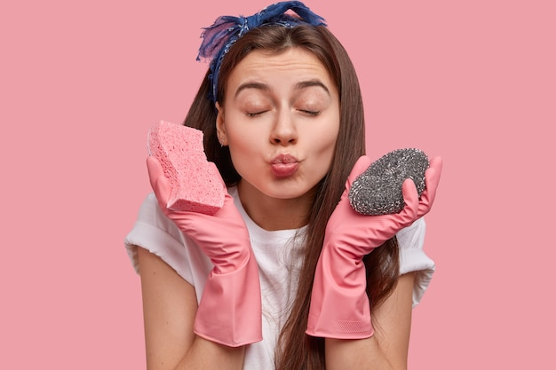 Photo of atractive woman with healthy skin, folded lips, closes eyes, wants to kiss someone, carries two sponges for washing up, wears rubber pink gloves