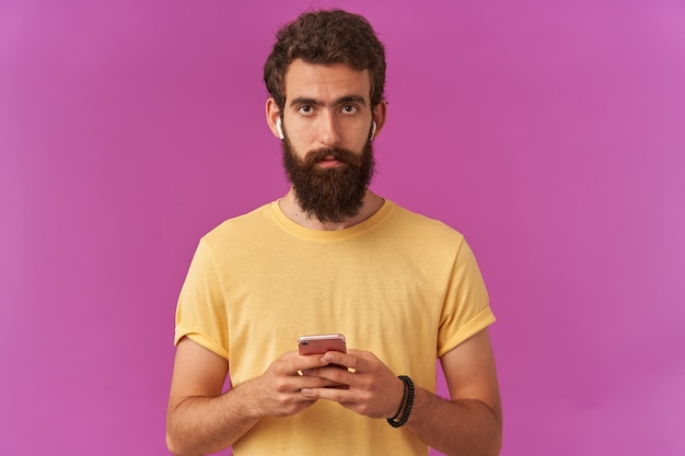Photo of attentive handsome bearded young guy hold phone with headphones in hands, concentrated standing over purple wall