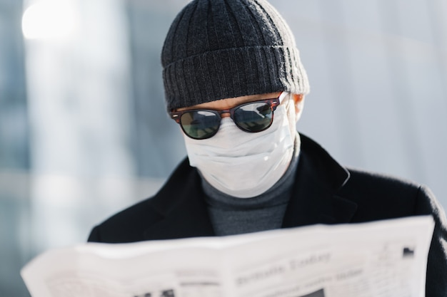 Photo of attentive man wears blak sunglasses, hat and against blurred background