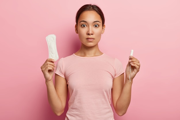 Photo of attractive asian woman holds cotton tampon and sanitary napkin, has surprised look, monthly menstrual cycle, wears pink t shirt. protective care for womens health. fertilization concept