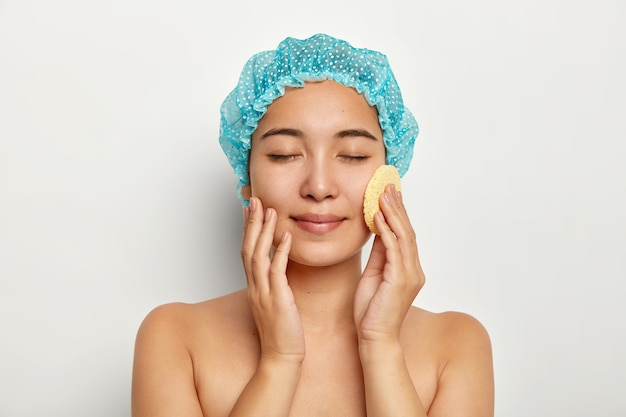 Photo of attractive asian woman washes face with cosmetic sponge, cleanses face, stands topless, keeps eyes closed, wears blue bathcap