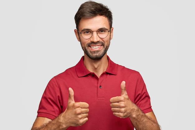 Photo of attractive bearded young man with cherful expression makes okay gesture with both hands, likes something, dressed in red casual t-shirt, poses against white wall, gestures indoor