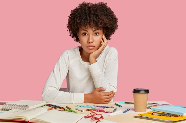 Photo of attractive black designer with afro haircut, sits at workplace, wears white jumper, makes drawings with crayons, isolated over pink wall, enjoys coffee