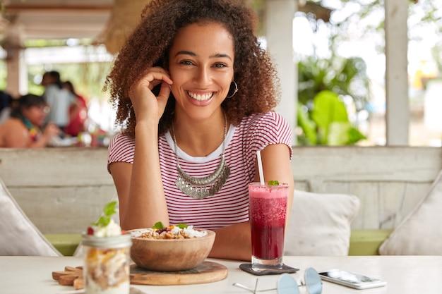 La foto della donna di colore attraente ha acconciatura afro