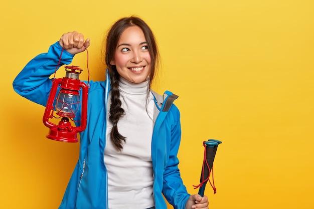 Foto di attraente donna bruna con espressione felice pensierosa, tiene in mano una lampada a gas rossa, bastoncini da trekking, copre lunghe distanze su un sentiero di montagna, indossa dolcevita e giacca blu, ricorda un momento piacevole