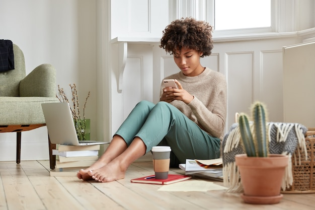 Photo of attractive busy woman has bushy hair, reads business data on cell phone, prepares for session
