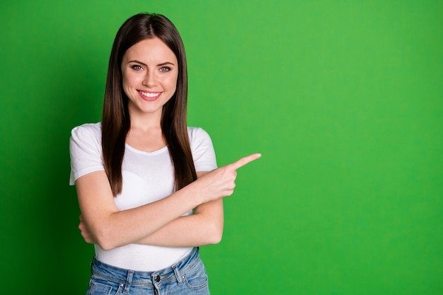 Photo of attractive confident young lady wear casual outfit arms crossed pointing empty space isolated green color background