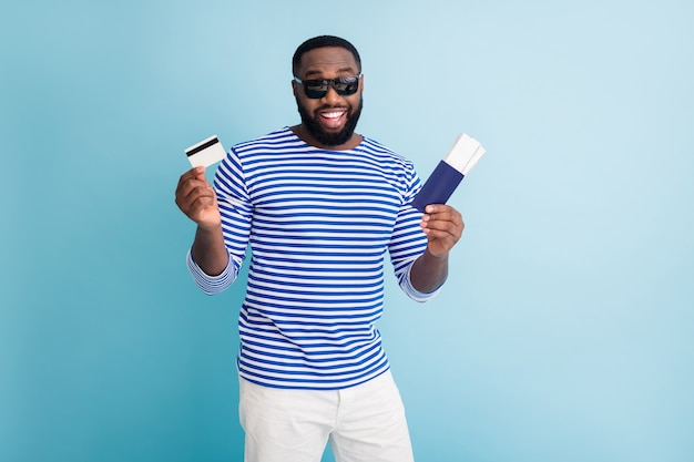 Photo of attractive dark skin guy traveler buy tickets with help of visa credit card wear sun glasses striped sailor shirt vest white shorts isolated blue color wall