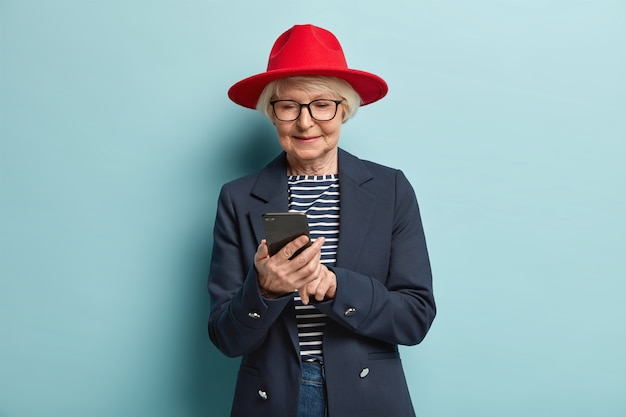 Photo of attractive elderly woman waits for feedback, concentrated in cell phone, being real shopaholic, wears red hat and formal clothing, isolated over blue wall, reads received message
