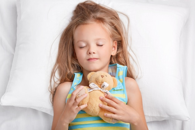 Photo of attractive female child has pleasant dreams at night, holds teddy bear, dressed in pajamas, sleeps in bedroom on comfortable bed. small child with favourite toy has rest. childhood concept