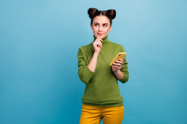 Photo of attractive funny lady hold telephone look up empty space think over writing new post arm on chin wear green turtleneck yellow trousers isolated blue color wall