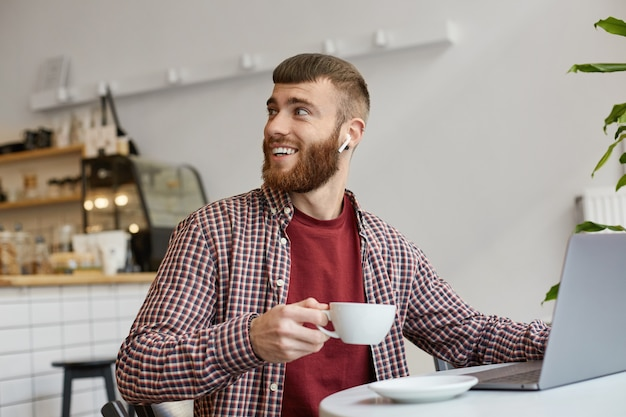 Photo of attractive ginger bearded man working at a laptop while sitting in a cafe, drinking coffee, wearing in basic clothes, looking back, thanks barista for a wonderful coffee.