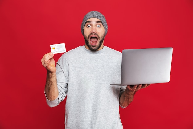 Photo of attractive guy 30s in casual wear holding credit card and silver laptop isolated