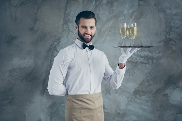 Photo of attractive handsome man with hand behind his back smiling toothily with bristle on face holding tray with glasses of champagne isolated grey concrete wall