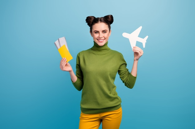 Photo of attractive lady hold paper air plane passport tickets advising flying way of traveling addicted traveler wear green turtleneck yellow trousers isolated blue color wall