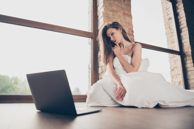 Photo of attractive lady quarantine stay home covered white blanket naked shoulders sensual look notebook undressing boyfriend video call touch lips teasing sit floor living room indoors