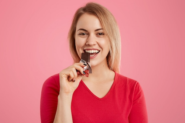 Photo of attractive light haired european young woman eats delicious sweet chocolate, being sweettooth